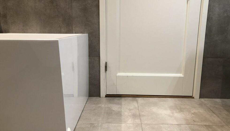 <strong>UTSATT FOR RÅTE:</strong> Dette badet er bare tre år gammelt, men allerede har det oppstått et begynnende råte-problem nederst ved listen langs døren. Årsaken er høyst sannsynlig vannsprut fra badekaret som er plassert i kort avstand fra døren. Foto: Linn Merete Rognø.