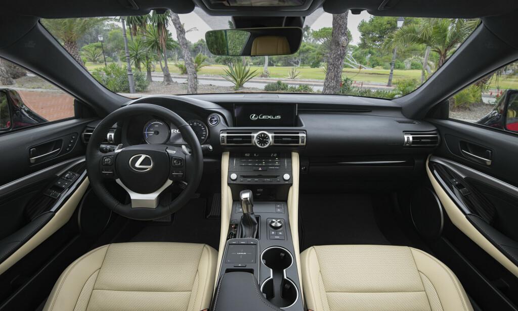 FORSEGGJORT: Med unntak av noen plastdetaljer som avslører Toyota-opprinnelse, er det stramt designede førermiljøet høyverdig og nennsomt utformet. Dreiehjulet med knapper ved siden betjener kjøreprogrammene - berøringsflaten ved koppholderne gir plundrete multimedie-betjening. Foto: Lexus
