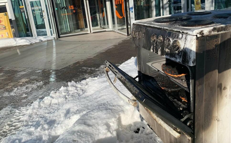 SVIDD PIZZA VED KJØPESENTER: Mange har lurt på hva de brente ovnene med tørrkokte kjeler og svidd pizza har gjort på steder som dette. Det er altså verken kunst eller hensatt søppel: Det er en kampanje for å vekke oppmerksomhet rundt hva en tørrkokt kjele kan gjøre av skade, i forbindelse med Komfyrvaktdagen 13. februar. Foto: Mosseregionens interkommunale brann og redning (MIB)