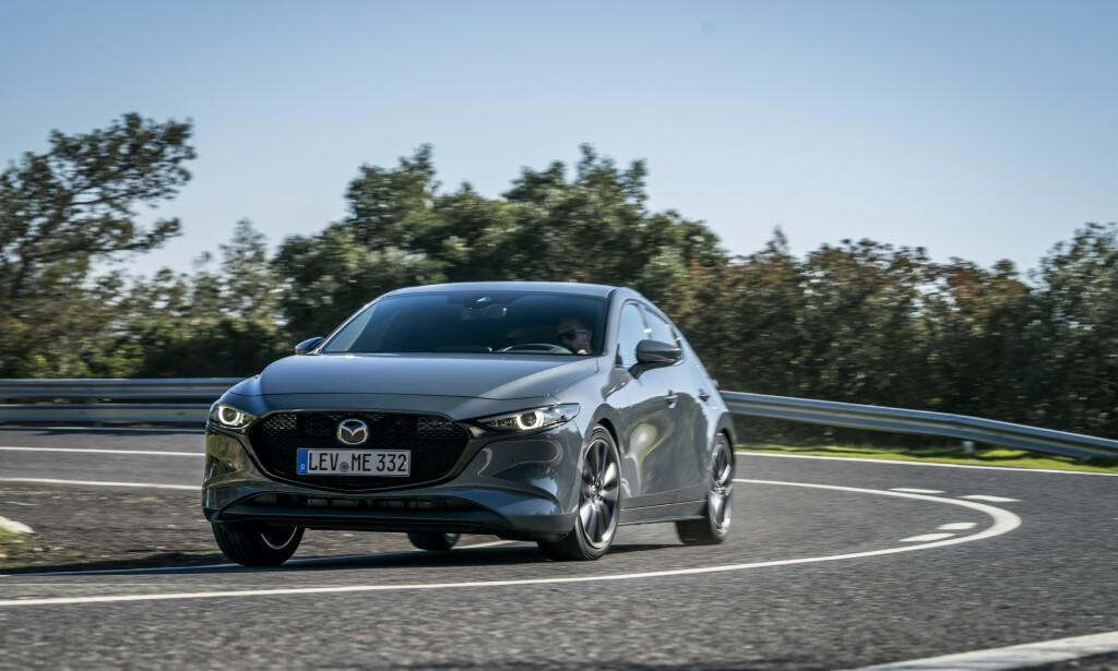 PEKER SEG UT: Nye Mazda 3 er etter vår mening svært vellykket i linjeføring og designspråk. Man kan selvsagt være uenig, men kjedelig er den i hvert fall ikke - selv i grått, som her. Foto: Mazda