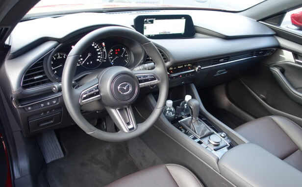 FØRER-SENTRERT: I tråd med Mazdas filosofi om at mennesket og kjøretøyet skal være som én («Jinba Ittai»), er alt plassert ergonomisk førervennlig. Mazda 3 har til og med head-up display som projiserer vesentlig informasjon i frontruten. Foto: Knut Moberg