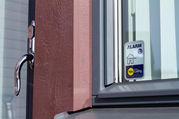 MERKING: Med basestasjonen følger det dobbeltsidige klistremerker som tydelig viser at hjemmet er beskyttet med en tilkoblet alarm. Foto: Tron Høgvold