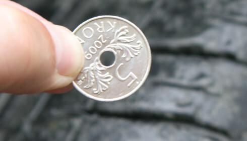 MØNSTERET: Med en fem-krone kan du måle mønsterdybden. Dekk med mindre mønster enn til toppen av fem-tallet (3 mm.) anbefales ikke. Foto: Rune Korsvoll