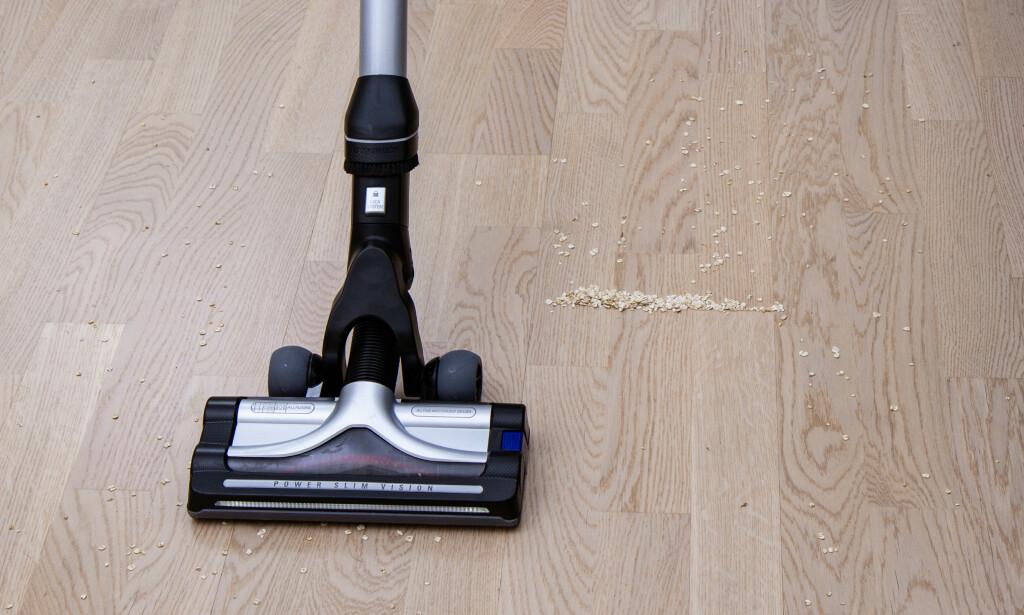 GRYN: Støvsugeren er i all hovedsak veldig bra på harde gulv, men den plukker ikke med seg større partikler når du drar den mot deg. Kun når den dyttes vekk, tar den med seg havregrynene. Foto: Tron Høgvold
