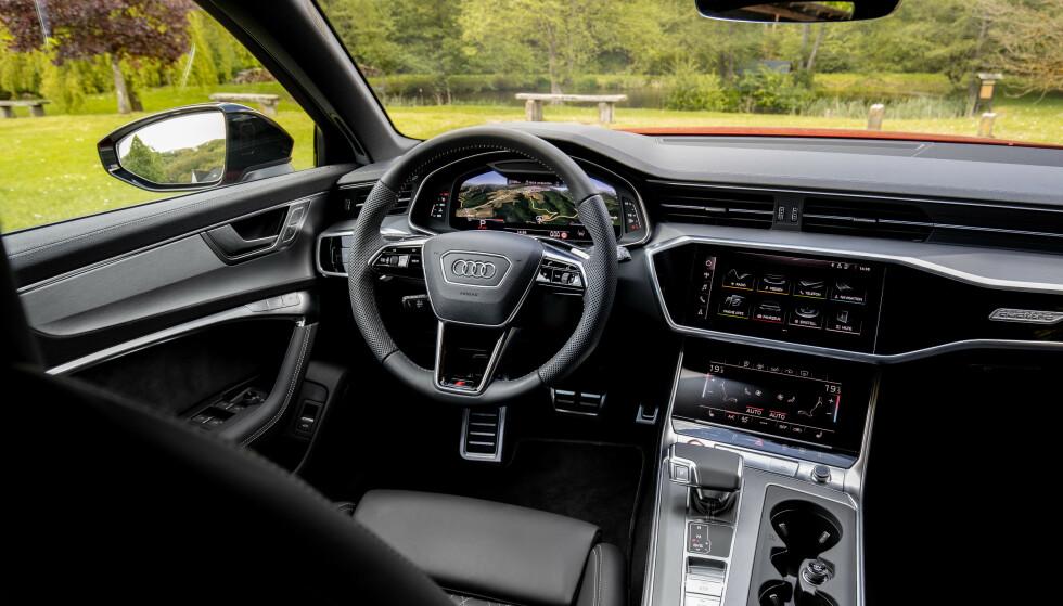 BUSINESS AS USUAL: Det sterile interiøret, med tre skjermer, er så og si identisk med A6, men materialvalget som er standard er her ekstrautstyr i A6. Foto: Audi