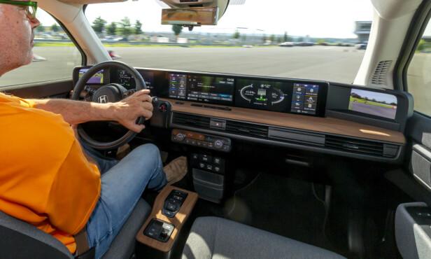 HØY TRIVSELSFAKTOR: En vag inspirasjon fra 70-tallet kombineres med den nyeste digitale teknologi. I dashbordet dominerer den brede skjermen - i virkeligheten tre separate skjermer som kommuniserer seg i mellom. Grovfibret tekstil og treverk skal ifølge produktutviklerne bidra til å gi bilen et hjemmekoselig preg. Foto: Manuel Portugal