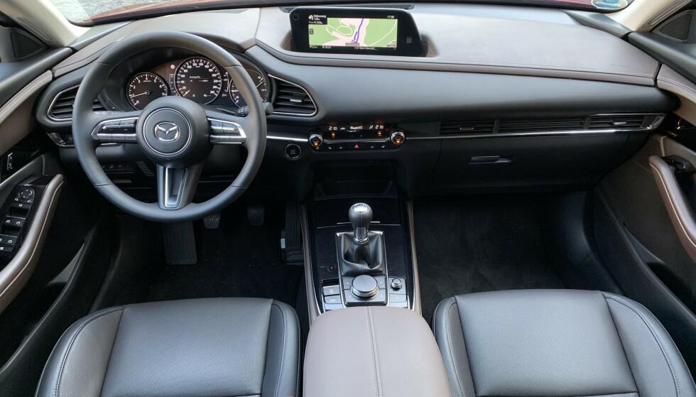 <strong>PREMIUM-ATMOSFÆRE:</strong> Kvalitetsfølelsen er påtakelig. Materialvalg, design og detaljarbeid - alt føles riktig. Alt er dessuten plassert ergonomisk førervennlig og vi kan bare lovprise betjeningen via dreiehjul, et logisk oppbygd menysystem og en tidsriktig, høyoppløst skjerm plassert i synsfeltet. Som Mazda 3 har CX-30 «ekte» head-up display (HUD), som projiserer vesentlig informasjon i frontruten. Foto: Knut Moberg