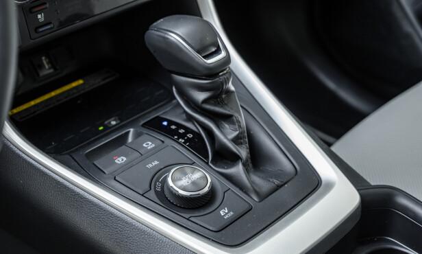 FLERE MULIGHETER: Nå har det tilkommet en knapp for TRIAL. Det sikrer drift på bakhjulene i oppstarten. Man har et dreiehjul for de tre kjøreprogrammene Eco, Normal og Sport. Hvorfor den ikke har standardoppsett på Eco, kan man jo undre på, når økonomi er hele grunnen for å kjøpe en hybrid. EV-knappen som skal sikre elektrisk kjøring, er like latterlig som den alltid har vært. Den virker kun unntaksvis. I en bil som dette trenger man egentlig ikke tradisjonell girspak. En digital løsning hadde satt bilen i Park av seg selv når man stopper bilen. Foto: Jamieson Pothecary