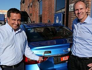 RSA-ansvarlig for nye bilmerker, Espen Kristoffersen (fra venstre) og RSA-sjef Frank Dunvold avduker den nye elbilen. Foto: Bilnytt