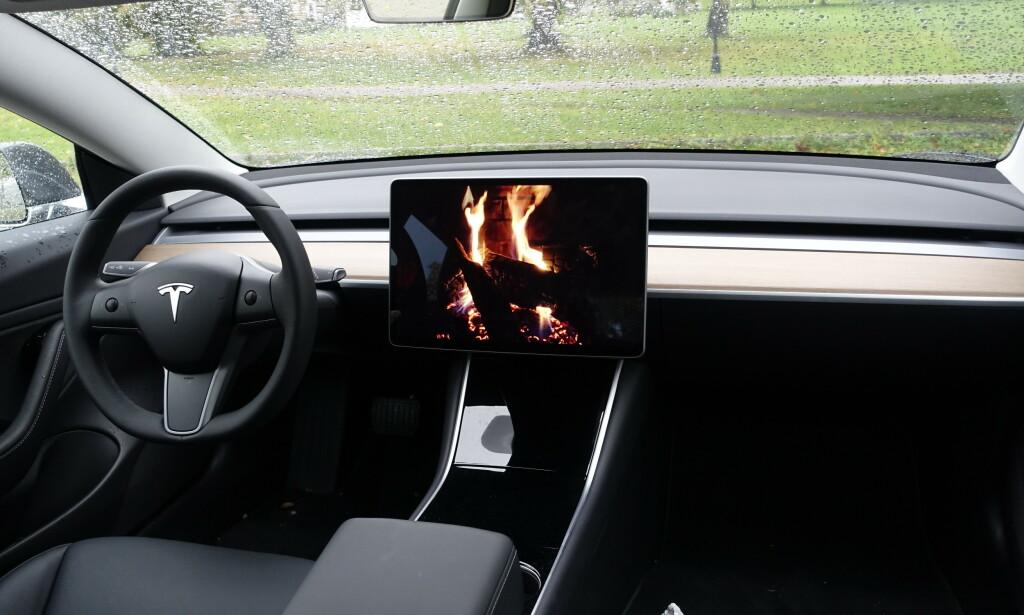 KOSELIG MED PEIS: Tesla er kjent for å ha litt humor i bilene sine. Som en knitrende peis for eksempel. Andre nyheter er Youtube og flere spill, til glede for store og små i ladekøen. Foto: Rune M. Nesheim
