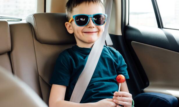 BLID MED BELTE: Ikke legg bilbeltet bak barneryggen. Hvis minsten klager på at beltet «skjærer» på halsen, går den an å kjøpe en beskyttelse å tre på beltet. Foto: Shutterstock/NTB Scanpix.