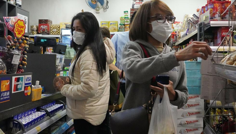 BESKYTTELSE: I Hong Kong går mange med munnbind om dagen for å hindre smitte av coronaviruset. Foto: AP/NTB Scanpix.