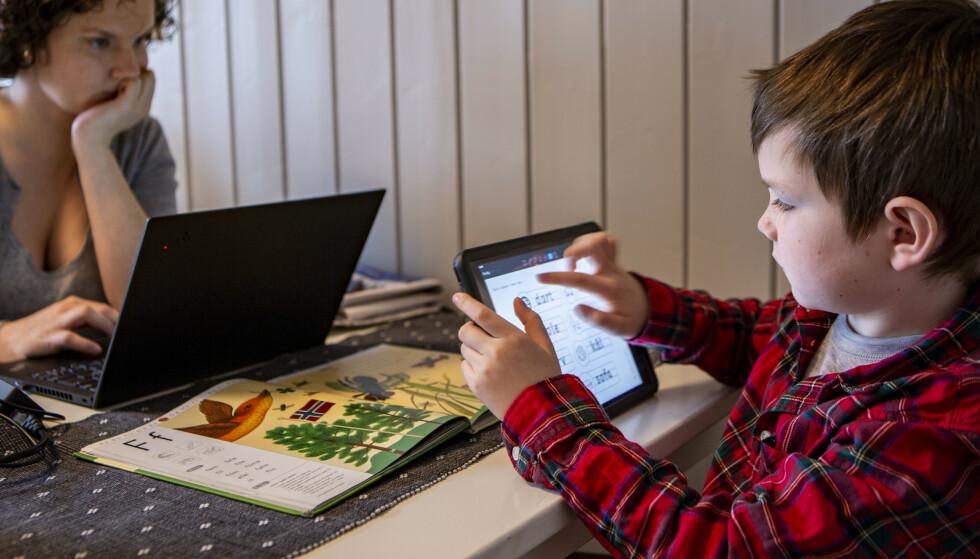 OMSORGSDAGER: 7 år gamle Paul Cornelis Kirkeby, som går i første klasse på koronastengte Vestli skole i Oslo, har hjemmeundervisning via iPad, mens mamma Anja Kristin har hjemmekontor. Nå endres blant annet reglene for omsorgsdager. Foto: Paul Kleiven/NTB Scanpix
