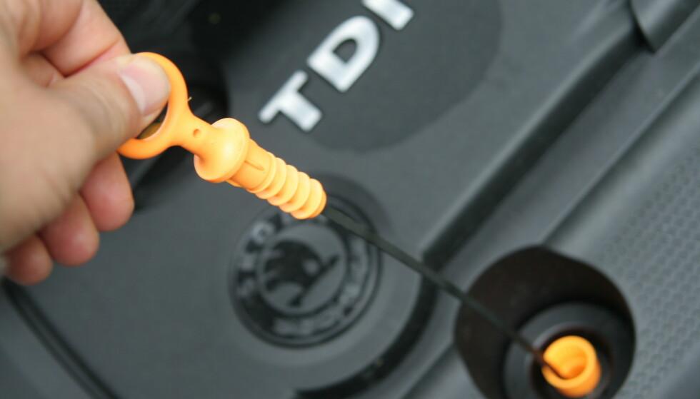 IKKE FARLIG: Det er helt ufarlig og svært enkelt å sjekke oljen på bilen manuelt. Peilepinnen viser tydelig om det er nok olje på motoren. Mellom maks og min merket går det på de fleste biler en liter. Foto: Rune Korsvoll