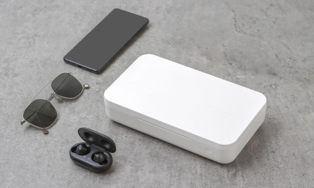 LADER OG DESINFISERER: Etter ti minutter i denne hvite boksen kommer telefonen ut nesten bakteriefri og med mer prosent på batteriet. Foto: Samsung