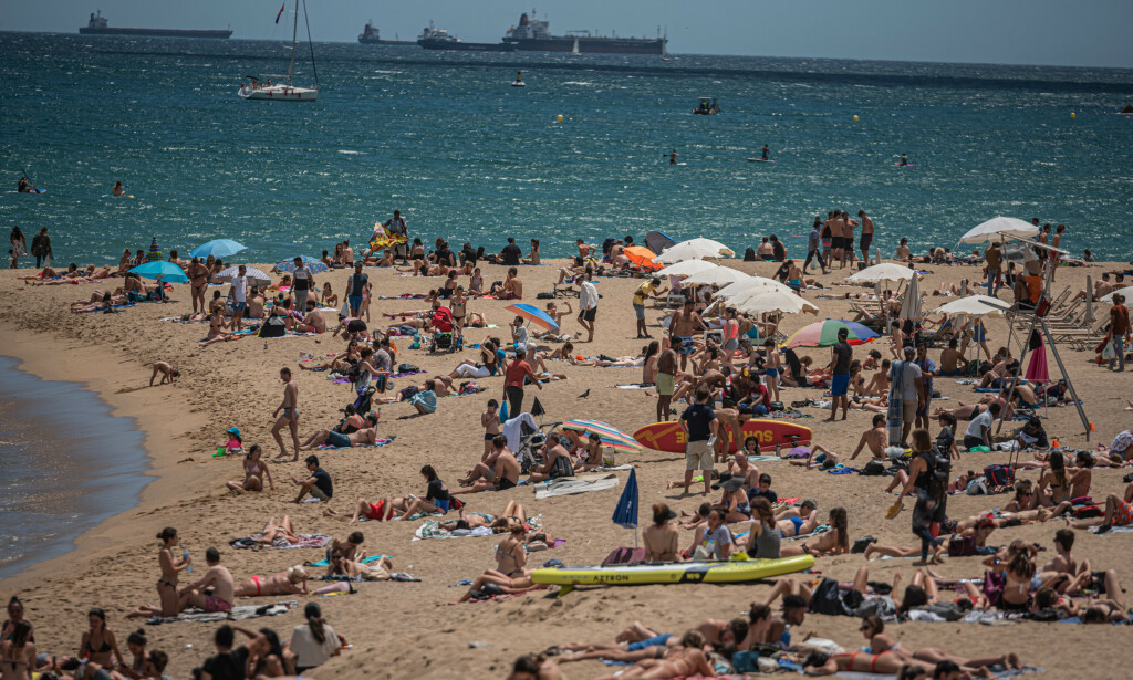 CORONA-TILTAK: Du bør belage deg på lokale coronatiltak hvis du skal ut og reise. Her fra en strand i Barcelona. Foto: NTB Scanpix/Gtres/Splashnews.com