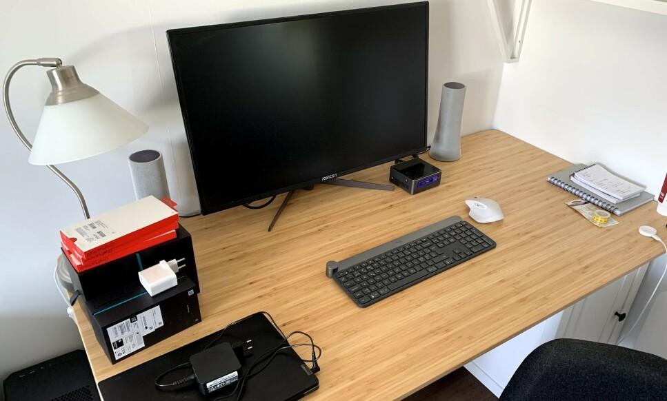 HJEMMEKONTORET: Slik ser det ut på hjemmekontoret til undertegnede. En romslig og dyp pult, en god og justerbar stol, tastatur, mus og stor, høyoppløst skjerm er det som skal til. Det behøver ikke koste all verden, men gjør det langt behageligere å sitte hjemme og jobbe. Foto: Bjørn Eirik Loftås