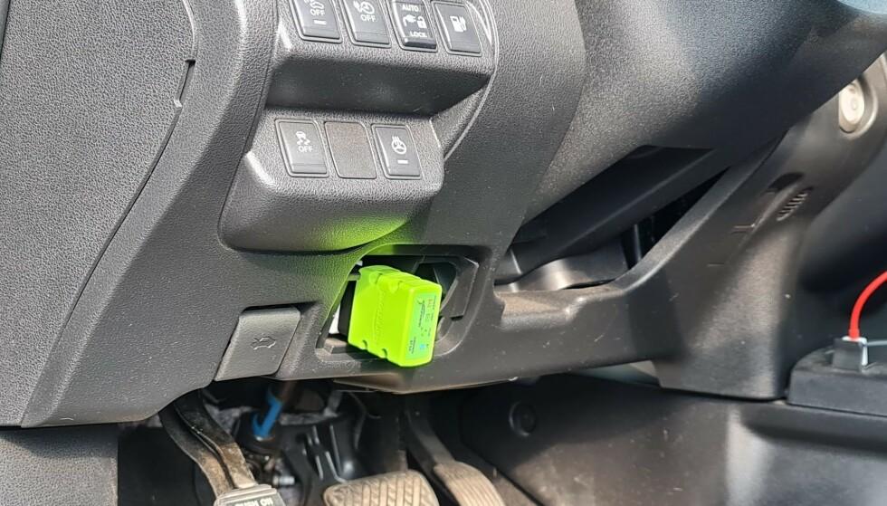 PLUGGES INN: Bak et lokk på undersiden av rattet finner du OBD-diagnoseporten. Ved å koble et egnet adapter inn her, kan du så bruke mobiltelefonen til å hente ut informasjon. Foto: Pål Joakim Pollen