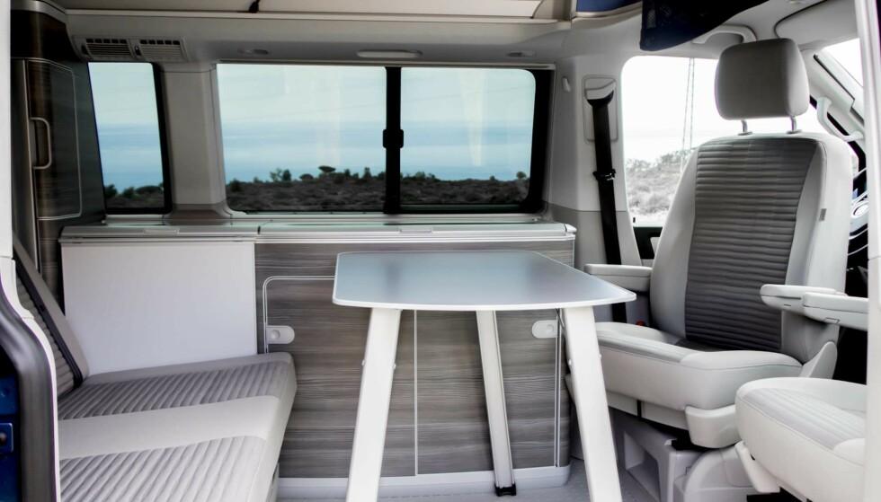 VW California. VW har tatt den lengst når det gjelder masse plass i kompakt bil. Her finner man både 230 volts anlegg, kjøleskap/fryser, vask, gass, masse skap og skuffer, hevetak og plass til fire innenfor fem meters lengde to meters høyde når taket er nede. Her ser man det store bordet oppfelt (har plass i skyvedøra når det ikke er i bruk). Det hvite feltet er et lite bord og i bakluka finnes to campingstoler. Foto: VW.