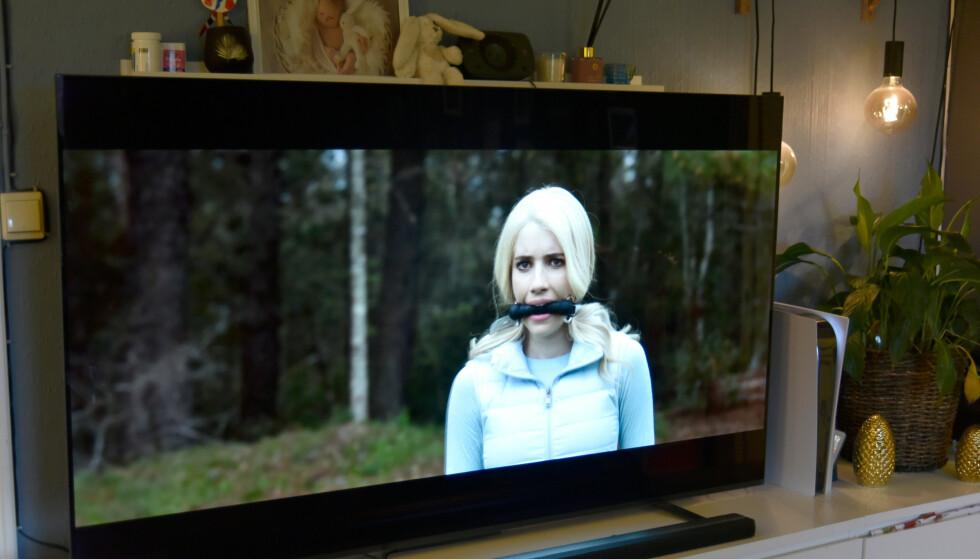 """Her er PS5 plassert ved siden av en 65"""" TV og er omtrent halvparten så høy. Foto: Pål Joakim Pollen"""