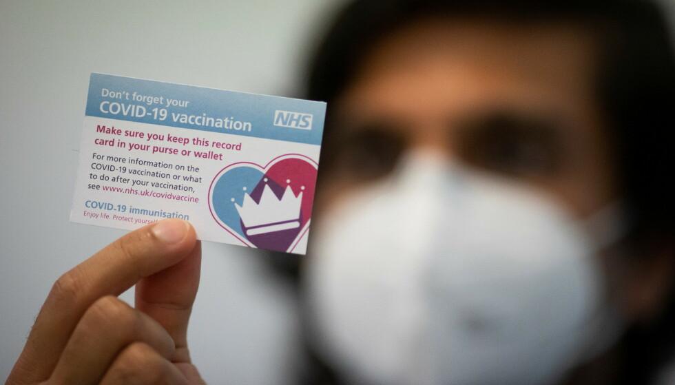 VAKSINEKORT: En ansatt ved Hurley-klinikken i London viser frem et vaksinekort. Foto: Aaron Chown/PA Wire/Pool via REUTERS