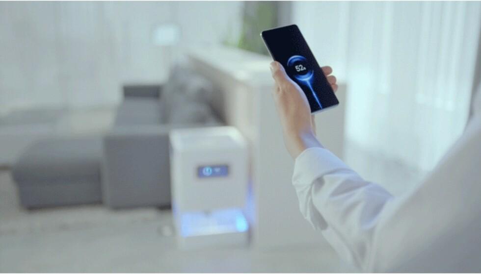 LADER: Her demonstrerer Xiaomi sin Air Charge-teknologi, som lar deg lade telefoner og andre enheter trådløst - over flere meters avstand. Foto: Xiaomi