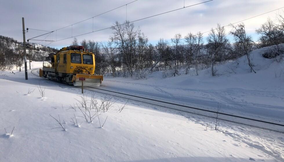 TOGSPOR SOM SKISPOR: Et arbeidstog jobber seg over vidda på Bergensbanen. Til høyre i bildet er synlig bevis for at skiløpere har gått vel tett på skinnegangen. Foto: Håkon Eggen/Spordrift AS