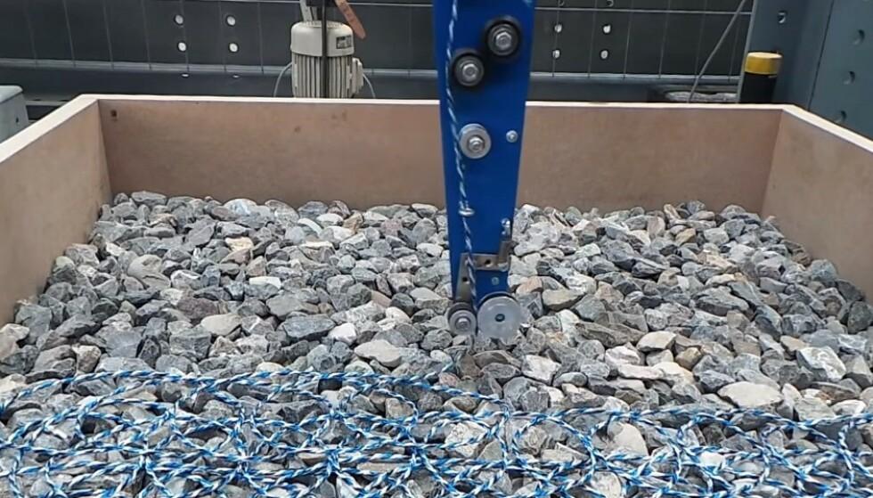 KAN RESIRKULERES: En robotarm «strikker» et nett av sterk tråd rundt steinene slik at de holdes på plass. Nå skal dette testes ut på vanlige veier. Foto: Empa