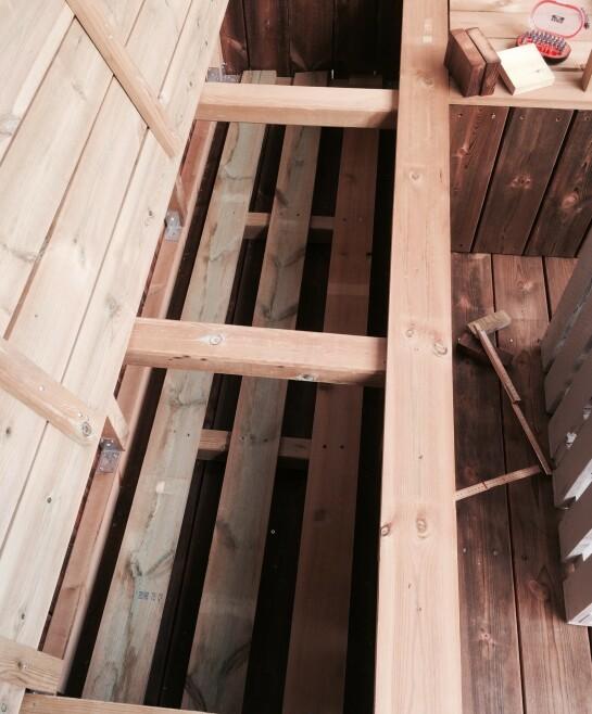 For at putene skal få lufting på undersiden, for å unngå sur lukt og fuktighet, la hun tre vanlige terrassebord nedi kassa.